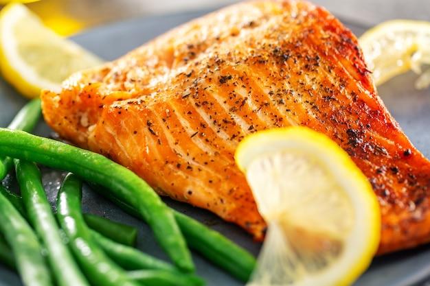 Nahaufnahme von gebackenen lachsfischen mit grünen bohnen
