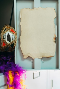 Nahaufnahme von gebranntem leerem papier auf schließfach der offenen tür mit karnevalsausrüstungen