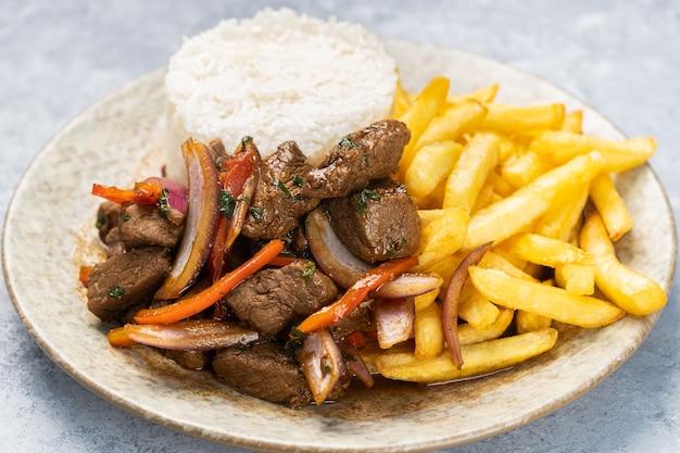 Nahaufnahme von gebratenem fleisch mit soße, gemüse und pommes in einem teller auf dem tisch