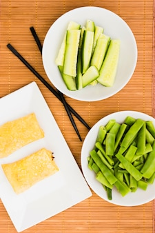 Nahaufnahme von gebratenen frühlingsrollen im behälter mit zucchinischeiben und flachen bohnen auf tischset