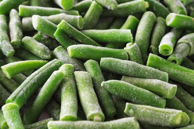 Nahaufnahme von gefrorenen grünen bohnen mit eis bedeckt. gefrorenes gemüse hintergrund.
