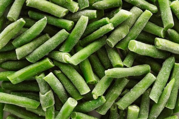 Nahaufnahme von gefrorenen grünen bohnen mit eis bedeckt. gefrorenes gemüse.