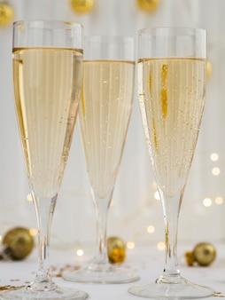 Nahaufnahme von gefüllten champagnergläsern mit goldenen kugeln
