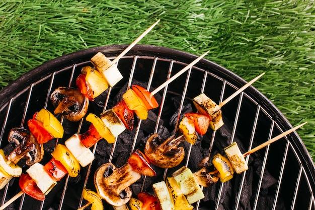 Nahaufnahme von gegrillten aufsteckspindeln mit fleisch und gemüse auf grill über matte des grünen grases
