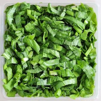 Nahaufnahme von gehackten grünen blättern salat in quadratischen gerichten texturoberfläche hintergrund