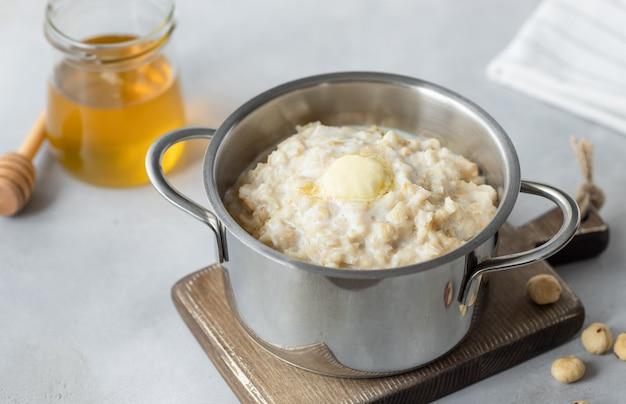 Nahaufnahme von gekochtem haferbrei in einer pfanne, haselnüssen und honig
