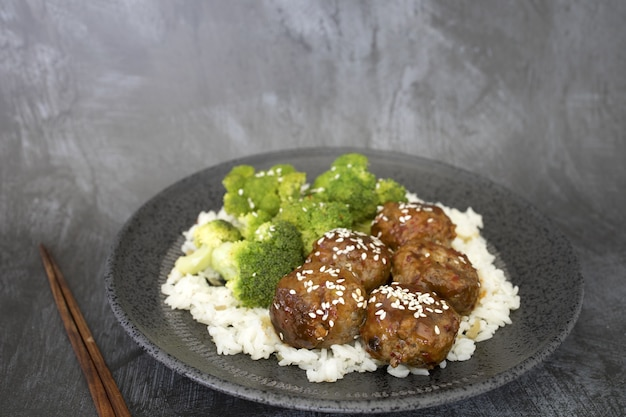 Nahaufnahme von gekochtem reis mit fleischbällchen und brokkoli in einem teller auf dem tisch