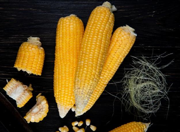 Nahaufnahme von gekochten ganzen und geschnittenen körnern mit maisseide auf schwarzer oberfläche