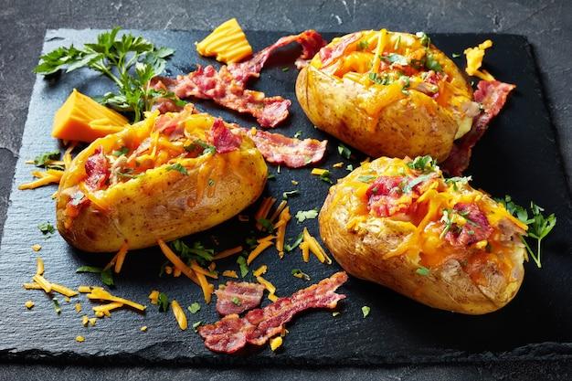 Nahaufnahme von geladenen frisch gebackenen kartoffeln mit speck, gezogener hühnerbrust und geschmolzenem käse auf einer schwarzen schieferplatte auf einem betontisch, horizontale ansicht von oben