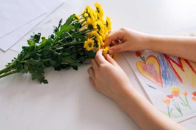 Nahaufnahme von gelben gänseblümchen und einer kinderzeichnung