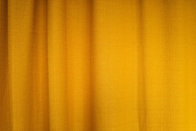 Nahaufnahme von gelben stoffvorhängen mit falten. abstrakter hintergrund, vorhang, drapiert goldgewebe.