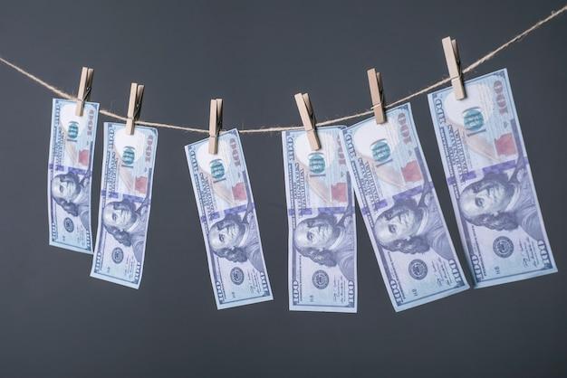 Nahaufnahme von geld, an den seilen getrocknet, mit wäscheklammern befestigt. das konzept des geldtrocknens.