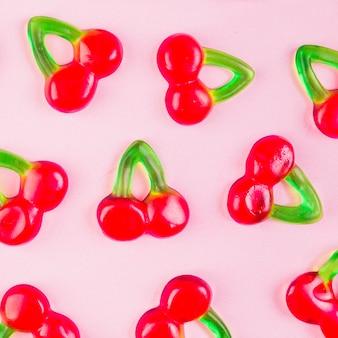 Nahaufnahme von gelee-kirschsüßigkeiten auf rosa hintergrund
