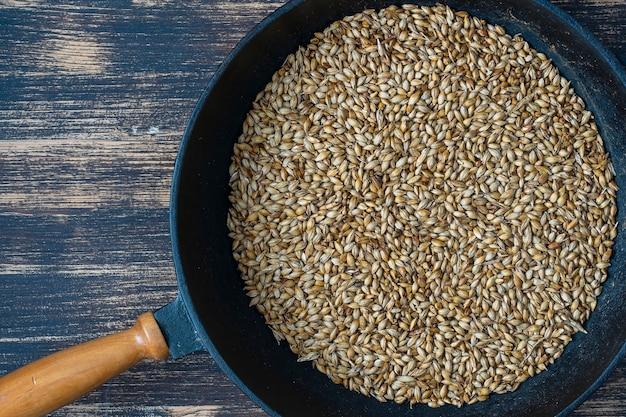 Nahaufnahme von gerösteten gerstenkörnern in einer gusseisernen pfanne auf dem tisch, ansicht von oben. zutat für bier oder kwas