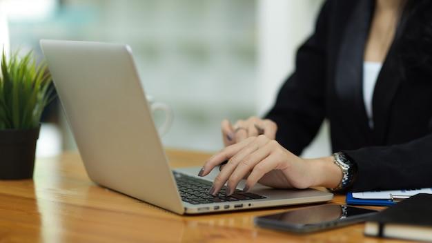 Nahaufnahme von geschäftsfrauen in schwarzen anzughänden, die auf der laptop-tastatur am arbeitsplatz tippen