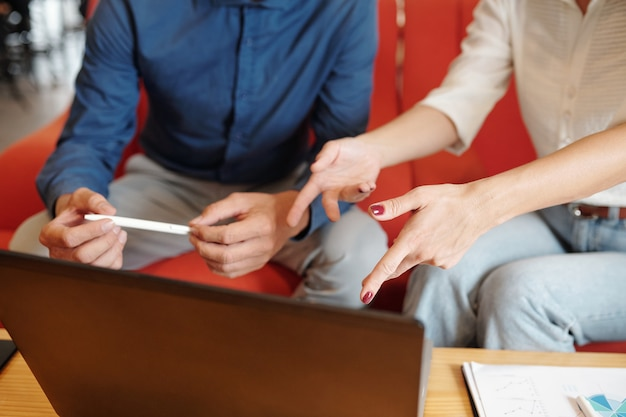 Nahaufnahme von geschäftsleuten, die auf den laptop-bildschirm zeigen, wenn sie einen bericht oder eine produktpräsentation diskutieren