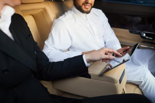 Nahaufnahme von geschäftsleuten, die digitales tablet im team während des fahrens im auto verwenden