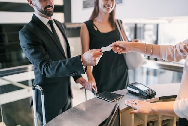 Nahaufnahme von geschäftsleuten macht kartenzahlung beim check-in an der rezeption.