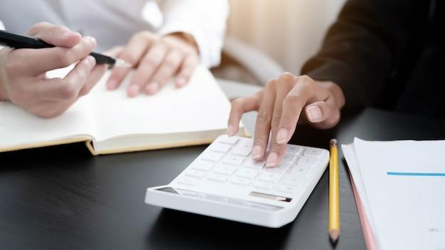 Nahaufnahme von geschäftsmann und frau mit taschenrechner und schreiben auf einem notebook im büro