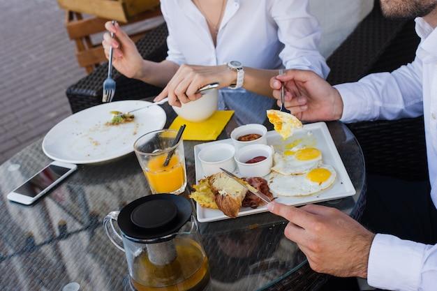 Nahaufnahme von geschäftsmannhänden, mann und frau, die frühstück im freiencafé haben. mahlzeiten mit salat, omelett, speck.