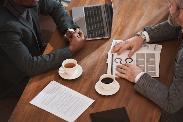 Nahaufnahme von geschäftspartnern, die mit tassen kaffee am tisch sitzen und mit dokumenten mit laptop arbeiten
