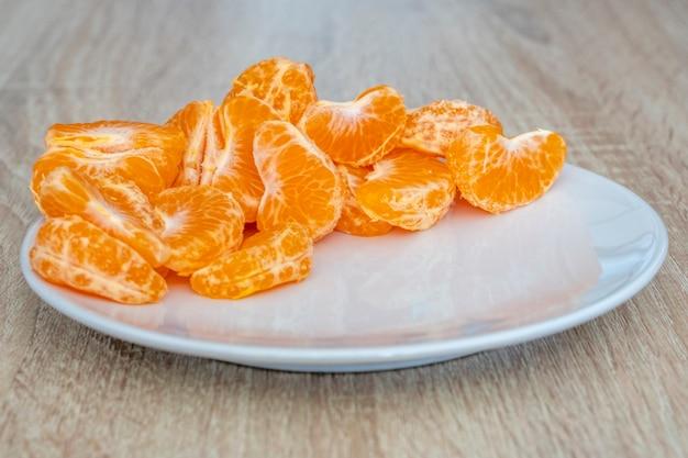 Nahaufnahme von geschälten mandarinenfrüchten auf weißem teller, hölzerner schreibtischoberfläche, kopienraum für text