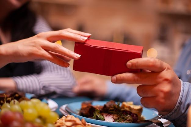Nahaufnahme von geschenkbox und paar beim romantischen abendessen