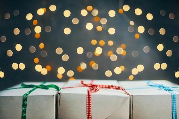 Nahaufnahme von geschenken stapel auf bokeh hellem hintergrund weiße kästen mit bunten bändern stehen in reihe neu ...