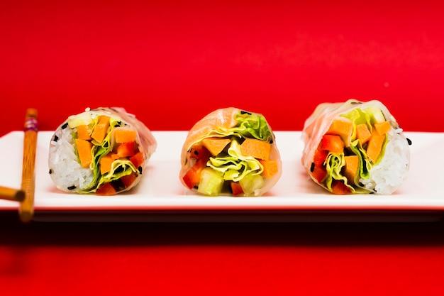 Nahaufnahme von geschmackvollen gemüsefrühlingsrollen auf behälter mit essstäbchen