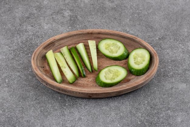 Nahaufnahme von geschnittenen frischen gurken in holzplatte