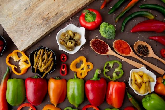 Nahaufnahme von geschnittenen, ganzen, gesalzenen paprikaschoten mit gewürzen, brokkoli
