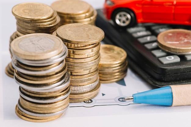 Nahaufnahme von gestapelten münzen; stift und taschenrechner