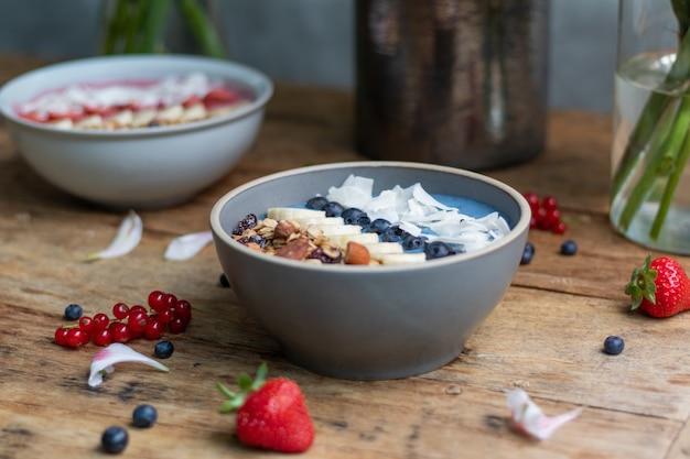 Nahaufnahme von gesunden smoothie-schalen mit früchten und müsli