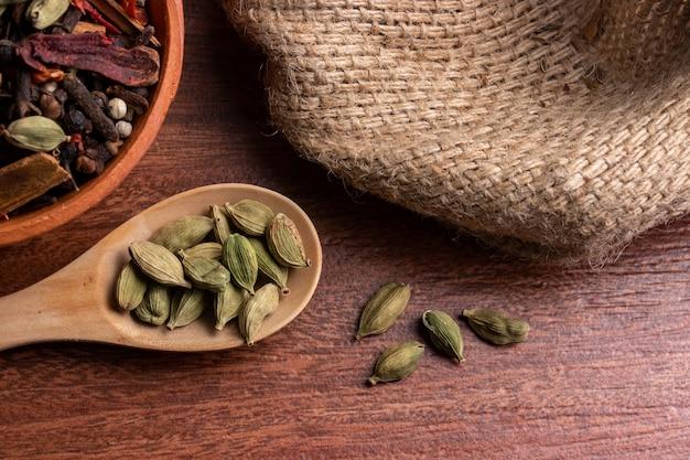 Nahaufnahme von getrockneten kardamomkapseln im löffel auf holzoberfläche, indisches gewürz zum kochen