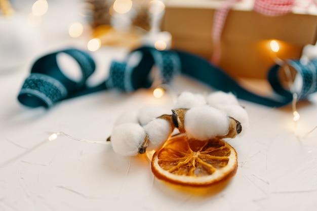 Nahaufnahme von getrockneten orangen- und baumwollweihnachtsdekorationen auf weißer tischbandgirlande und geschenkbox ...