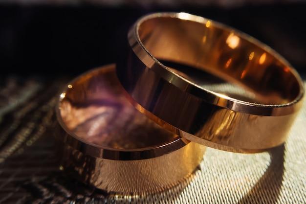 Nahaufnahme von glänzenden goldenen eheringen
