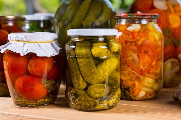 Nahaufnahme von gläsern mit konserviertem gemüse, frisch eingelegten gurken, paprika und tomaten auf holztisch