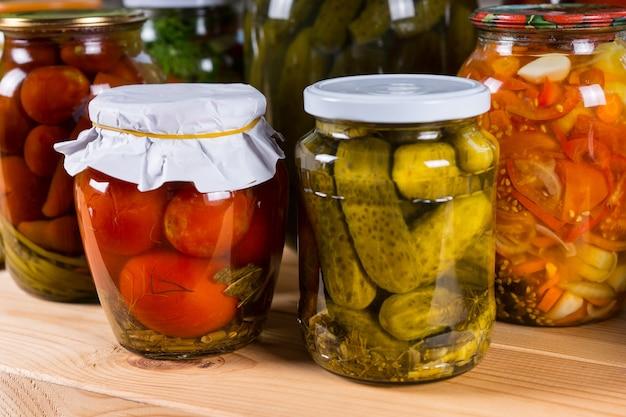 Nahaufnahme von gläsern mit konserviertem gemüse, frisch eingelegten gurken, paprika und tomaten