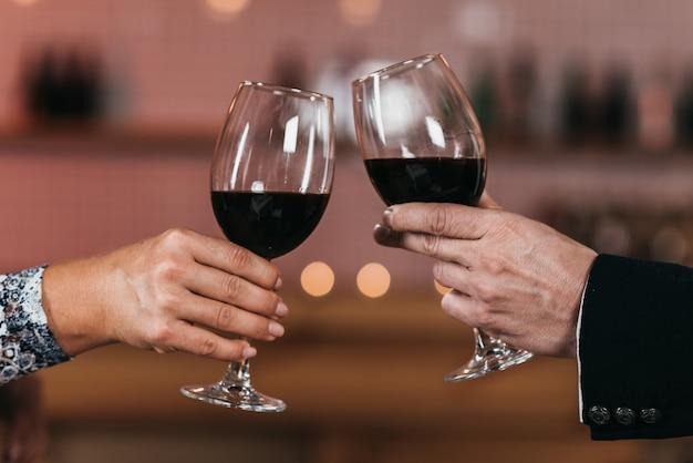 Nahaufnahme von gläsern mit rotwein in den händen eines mannes und einer frau in der mitte des rahmens
