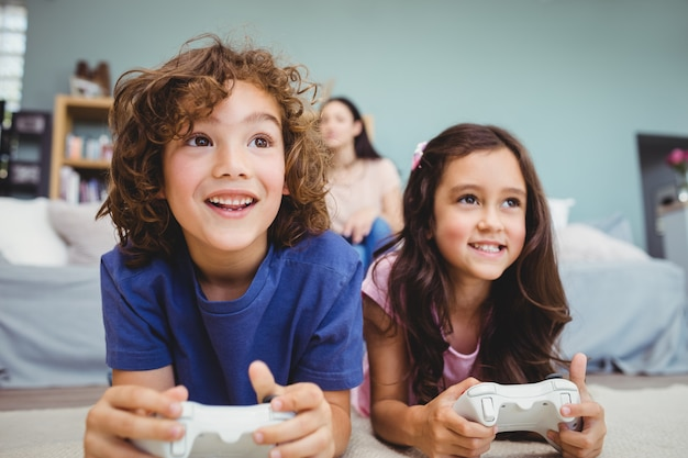 Nahaufnahme von glücklichen geschwistern mit den prüfern, die videospiel spielen