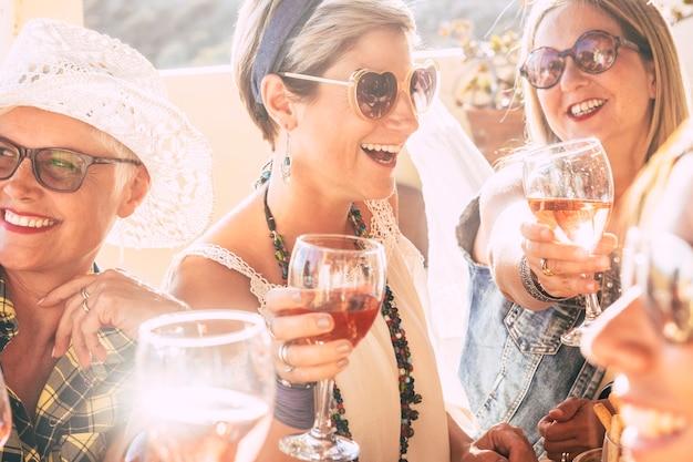 Nahaufnahme von glücklichen, schönen, fröhlichen menschen, die zusammen mit rotwein feiern - helles, sonniges bild, fröhlich und freundschaft - junge ältere damen, die lächeln und lachen und spaß auf der party haben
