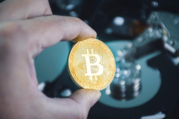 Nahaufnahme von gold-bitcoin in der hand mit festplattenplatten im hintergrund verschwommen