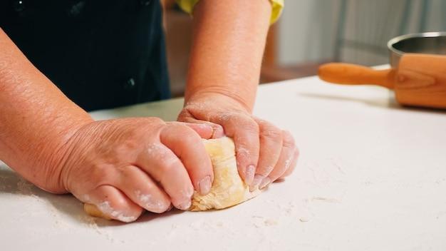 Nahaufnahme von großmutterhänden, die auf dem tisch in der heimischen küche kneten. pensionierter älterer bäcker mit bonete, der zutaten mit gesiebtem weizenmehl knetet, um traditionellen kuchen und brot zu backen.