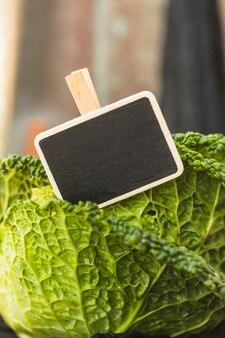 Nahaufnahme von grünen chinakohlblättern und von schwarzem schiefer