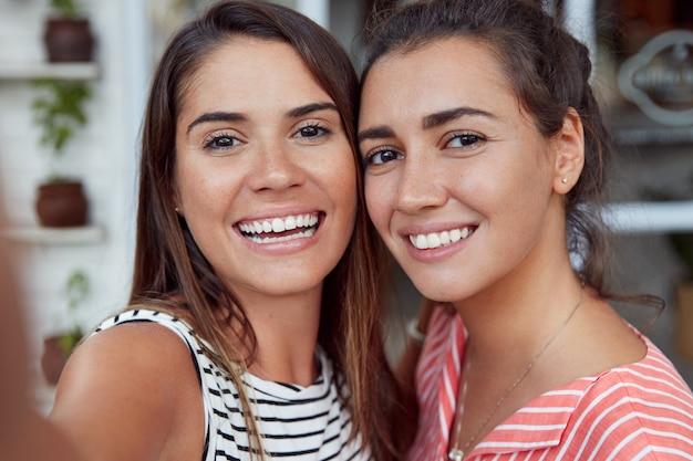 Nahaufnahme von gut aussehenden frauen mit breitem lächeln, posieren zusammen für selfie, haben erfreute ausdrücke. enge freundinnen fotografieren sich selbst, haben ein attraktives aussehen und wahrheitsgemäße beziehungen