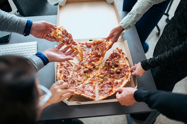 Nahaufnahme von hände, die scheiben pizza auf einer mittagspause nehmen.