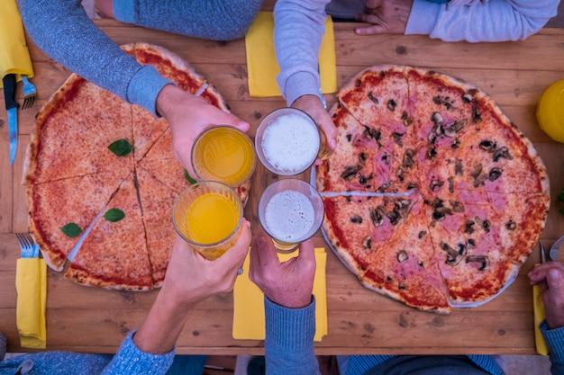 Nahaufnahme von händen mit glas mit bier und orangensaft, die in der mitte des tisches zusammenklirren - zwei große pizzen auf dem holztisch