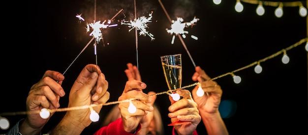 Nahaufnahme von händen mit wunderkerze und glas mit wein - leute tanzen auf einer party oder feiern das neue jahr zusammen mit der familie oder freunden