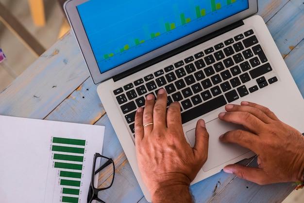 Nahaufnahme von händen schreiben und arbeiten mit laptop im büro auf einem blauen holztisch mit statistik und grafiken