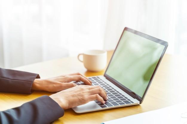 Nahaufnahme von händen von den geschäftsleuten, die mit laptop auf tabelle mit kaffeetasse arbeiten